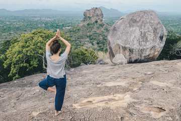 Back view of young woman doing Yoga on top of Pidurangala rock and looking to Sigiriya rock an...