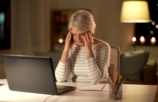 technology, old age and stress concept - tired or stressed senior woman with laptop computer having headache at home in evening