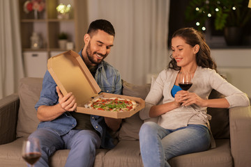 leisure, people and fast food concept - happy couple with wine eating takeaway pizza at home in evening