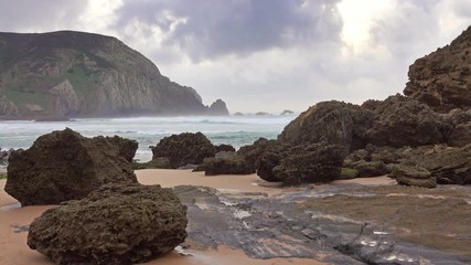 Wall Mural - Sandy beach and rocks with cloudy sky on Atlantic coast in Portugal, Europe, 4k