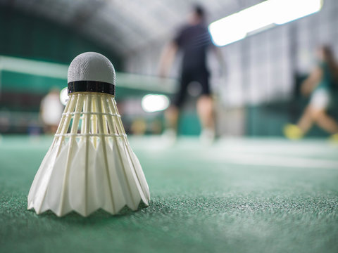 The shuttlecock is on the green badminton court floor. There is motion blur. The highlight is the badminton ball. There is space for the copy space.