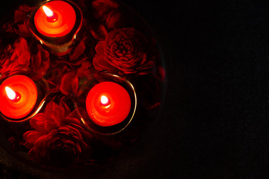 red candles in a candlestick on a black background, top view