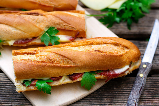 Oven baked baguette sandwich with cheese, ham and tomato