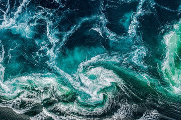 Fotobehang Natuur Abstract background. Waves of water of the river and the sea meet each other during high tide and low tide. Whirlpools of the maelstrom of Saltstraumen, Nordland, Norway