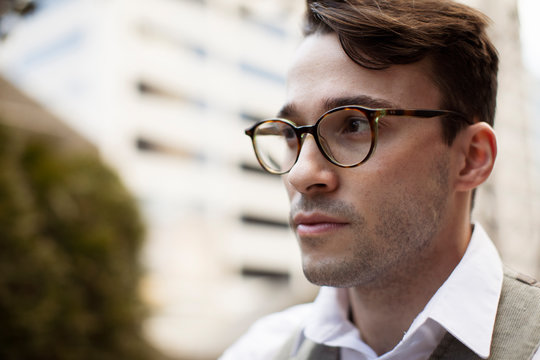 Close-up of thoughtful businessman wearing eyeglasses looking away while standing against building in city
