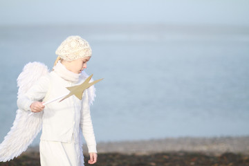 Girl in angel costum at the winter beach
