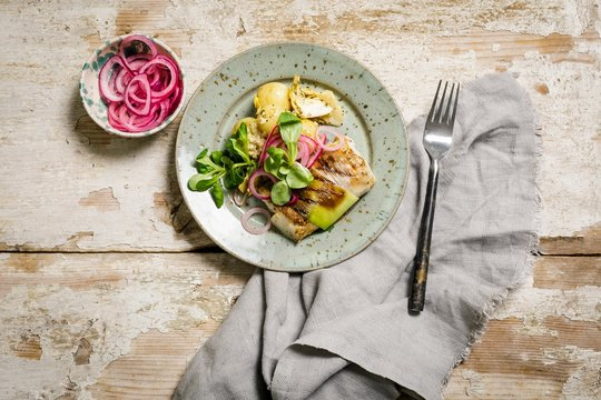 Zaatar baked cod in purjo with potato and pickled onions