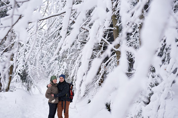 Fototapete - Young couple hugging while out hiking in a winter forest