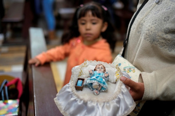 Woman carries a Jesus Christ figurine as a girl looks on, at the San Pedro Church on Three Kings' Day, or the Feast of the Epiphany, in La Paz