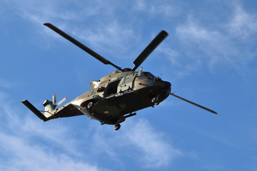 Photo sur Plexiglas Hélicoptère MILITARY HELICOPTER WITH A FOUR-BLADE ROTOR FLYING OVER AN AREA