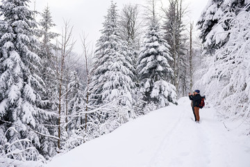 Fototapete - Couple photographing a snow covered landscape while hiking in winter