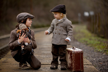 Adorable boys on a railway station, waiting for the train with suitcase and beautiful vintage doll