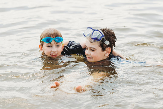 Brothers wearing swimming goggles in water hugging