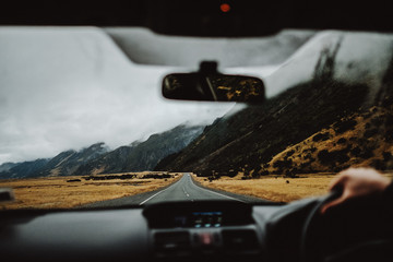 Driving a car in New Zealand with a mountain background in a moody day