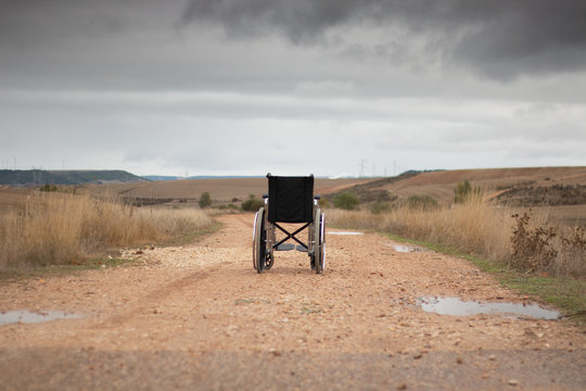 Rear vision of a wheelchair isolated in the middle of a path