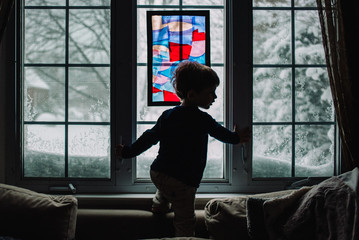 A little boy stands in front of a snowy window.