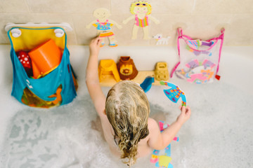 A little girl plays with toys in the bath.