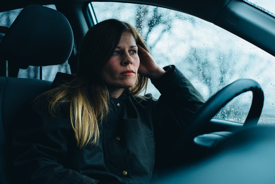 A woman sits in a car.