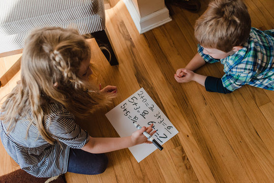A boy and girl practice math problems.
