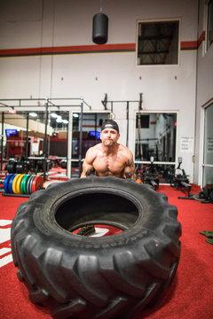 shirtless man flips large tire at the gym.