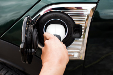 hand plugging in an electric car