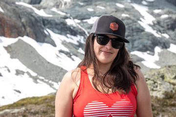 A women hiking in the mountain takes a break and smiles for the camera on a summer day in the mountains of British Columbia. Wall mural