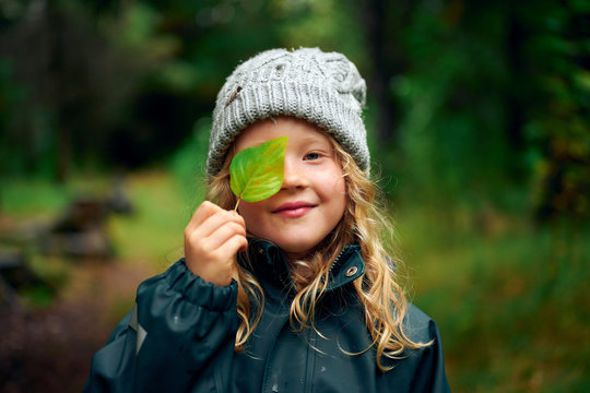 Long haired charming girl in warm hat closing eye with green leaf in forest