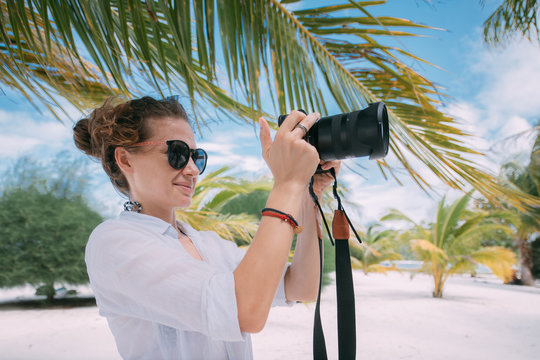 Girl photographer, videographer with a professional camera in the tropics.