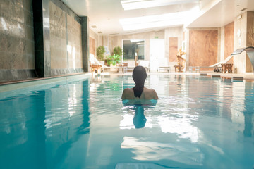 Rear view of a woman relaxing in spa pool