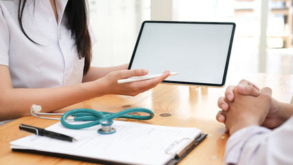 Doctor using tablet discussion something with patient.