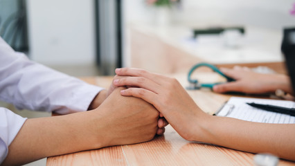 Doctor comforting patient at consulting room.