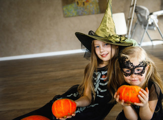 Two Sisters Dressed for Halloween in Skeleton Costumes with Pumpkins Wall mural
