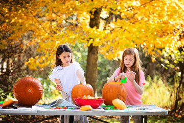 Two Young Girls Carving Pumpkins Outdoors Wall mural