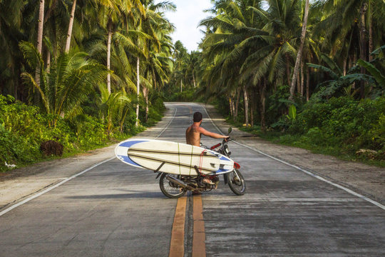 man riding motorcycle with surfboards in coconut road palms philippine