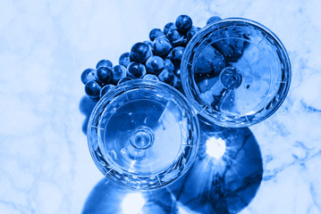 Two crystal stemmed glasses with prosecco on marble table outdoors in a cafe. Aperitif and relax time. Classic blue color of 2020 tone