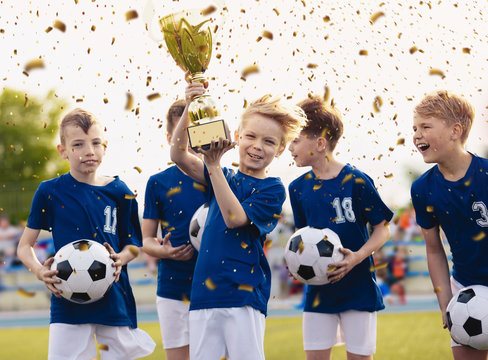 Happy kids in elementary school sports team celebrating soccer succes in tournament final game