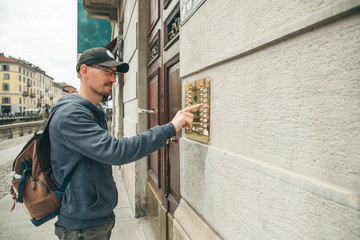 A guy or a man or a tourist presses a doorphone button to access inside.