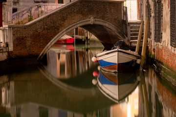 Aluminium Prints Venice docked boat on a picturesque water canal in Venice italy