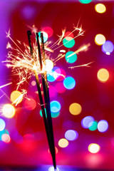 Glittering burning sparkler on red and color bukeh  background