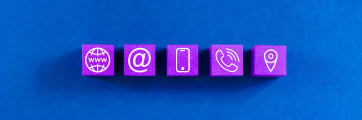 Wide view image of customer service image with five wooden dices with www, contact information and location icons on them. Over blue background.