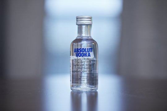 BUDAPEST, HUNGARY - CIRCA 2019: Absolut Vodka from Sweden on a table in a small bottle of 50 ml in window light