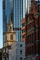 Traditional church and Modern Architecture. The St. Helen's Church and Norman Foster's Gherkin behind it in London's main financial district.
