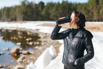 Beauty caucasian brunette woman in black jacket stay on the coast and drinking hot tea or coffee from thermo mug. Outdoor recreation. Nature tourism, Hiking. Winter season and active leisure concept.