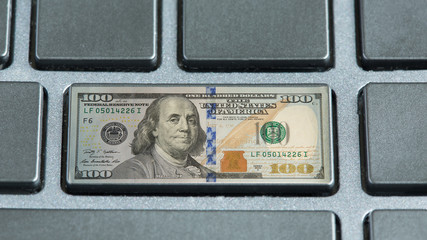 Macro photo of a keyboard. Instead of a key, enter $ 100. Concept of making money online.
