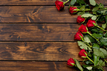 Door stickers Roses Red roses on a dark wooden background
