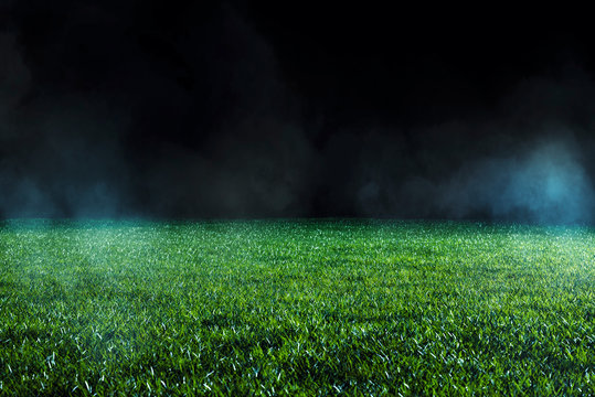 Spotlight shining on the green turf of an empty sports field at night.