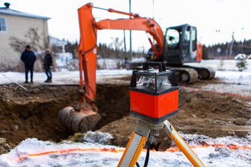 A selective focus view of a blurry excavator digging a hole on a construction site. ready for installation of septic tanks with laser level in front