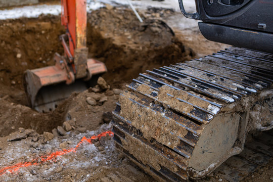 A close up view on the continuous tread of a mini excavator at work on a building site, using hydraulic arm to dig hole with copy space to left