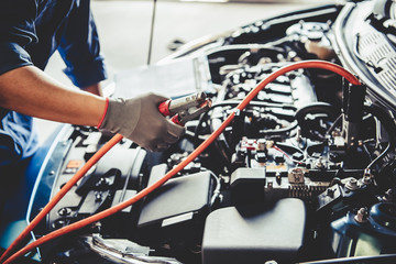 Car mechanic holding battery electricity trough cables jumper and checking to maintenance vehicle by customer claim order in auto repair shop garage. Repair service. People occupation and business job