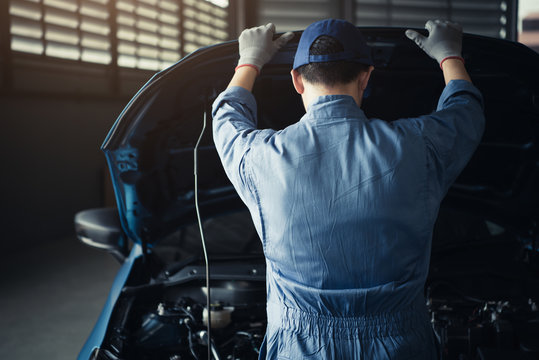 Car mechanic opening car hood for internal checking to maintenance vehicle by customer claim order in auto repair shop garage. Engine repair service. People occupation and job. Automobile technician